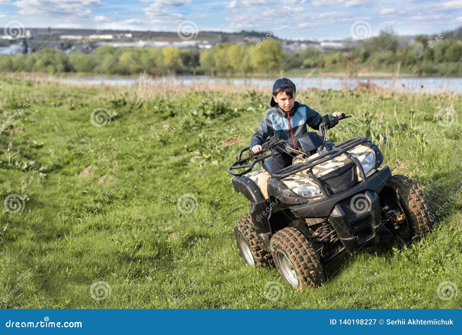 De jongen reist op een ATV