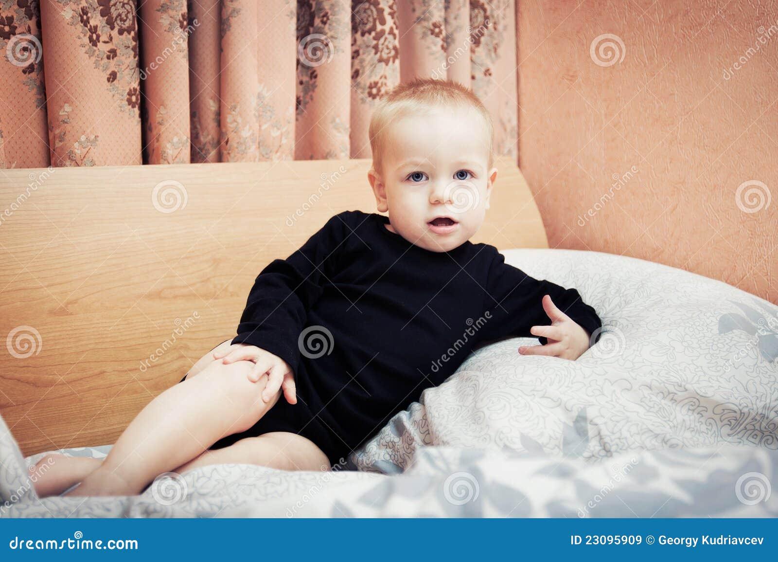 download de jongen van de baby het stellen op het bed van ouders in slaapkamer stock