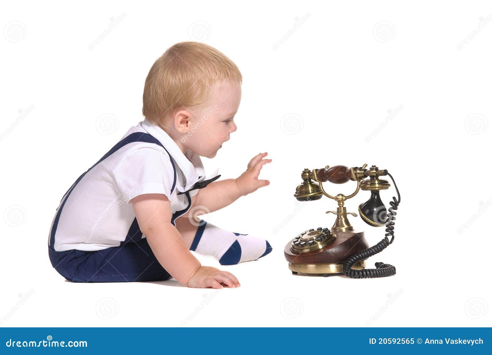 De jongen van de baby met ouderwetse telefoon