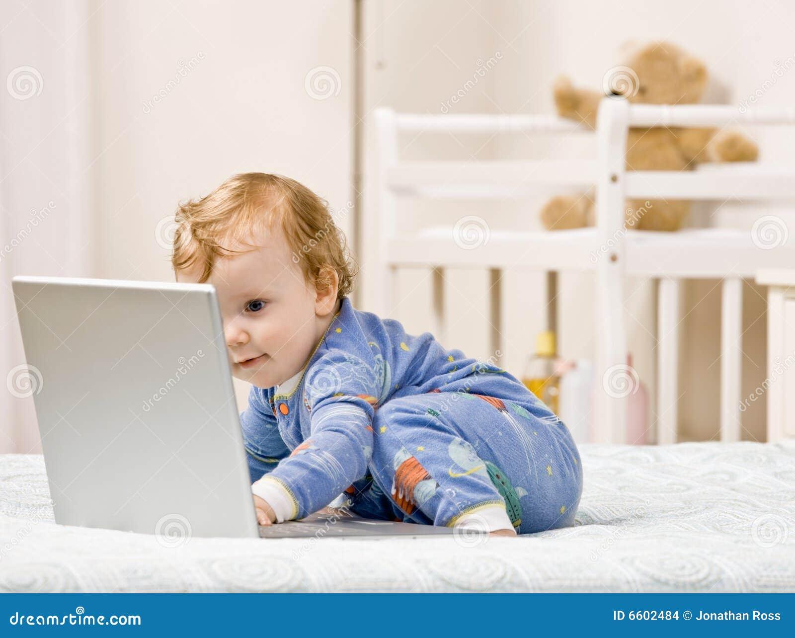 de jongen van de peuter het typen op laptop in slaapkamer
