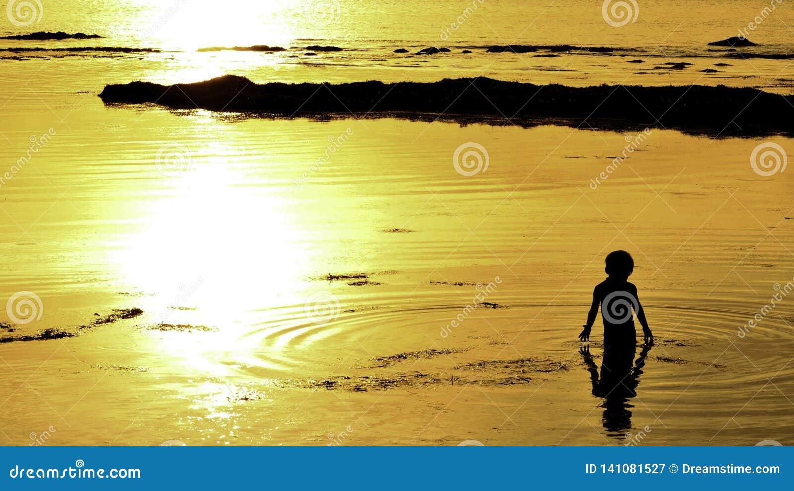 De jongen van het zonsondergangogenblik het spelen in water