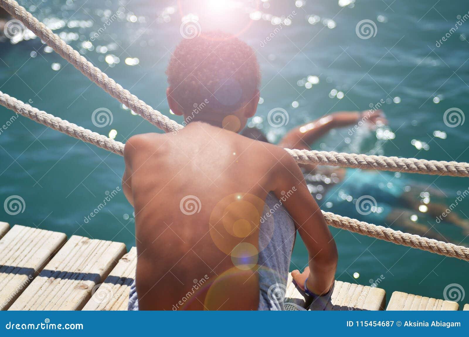 De jongen zit op de pijler en onderzoekt de afstand