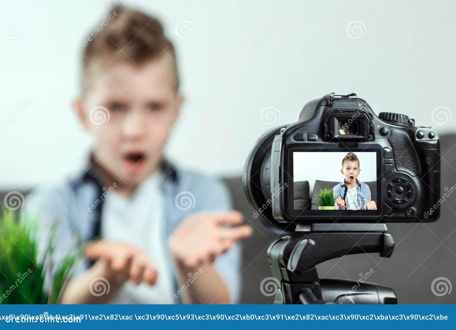 De jongen zit voor een SLR-camera, close-up Blogger, het blogging, technologie, inkomens op Internet De ruimte van het exemplaar
