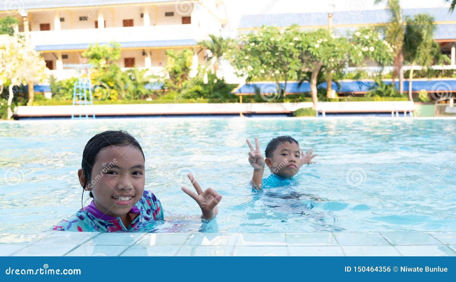 De jongens en de meisjes hebben pret het spelen in de pool