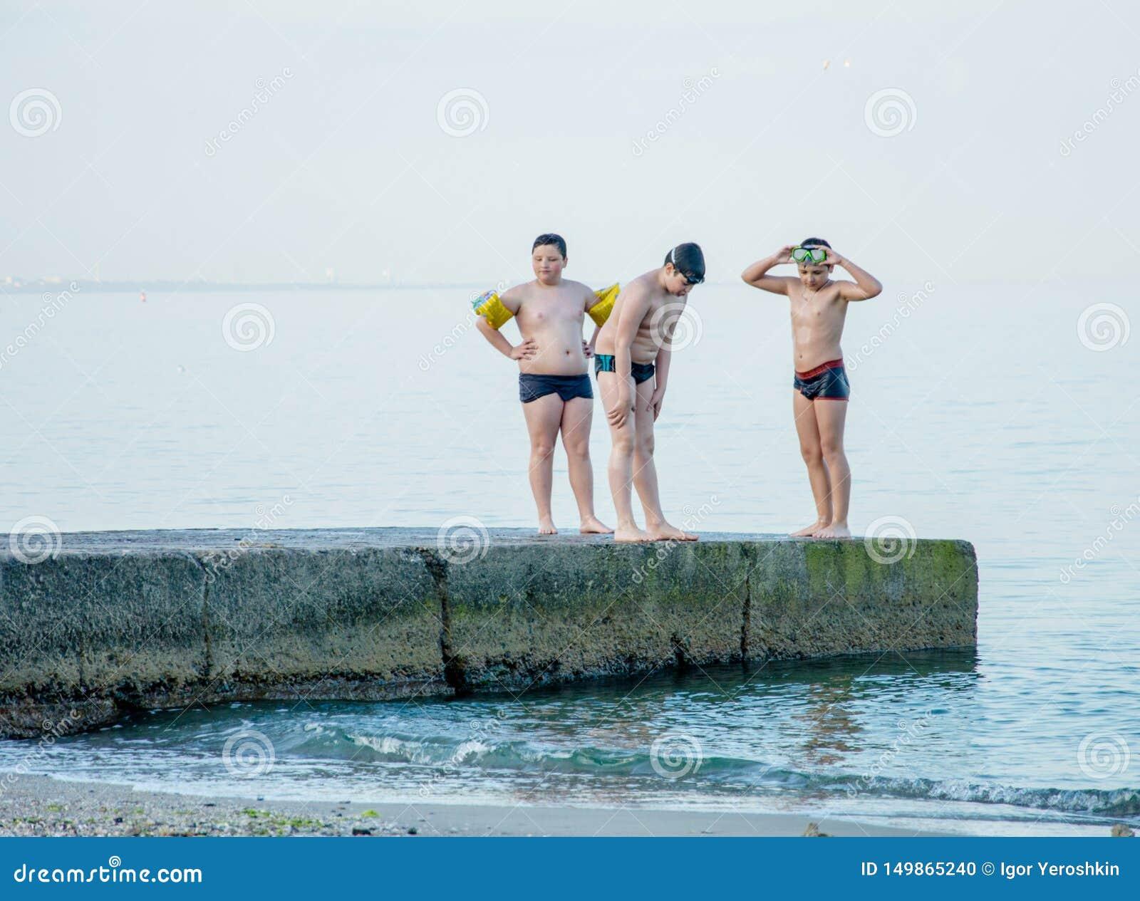 De jongens treffen om van de pijler in het overzees te springen voorbereidingen