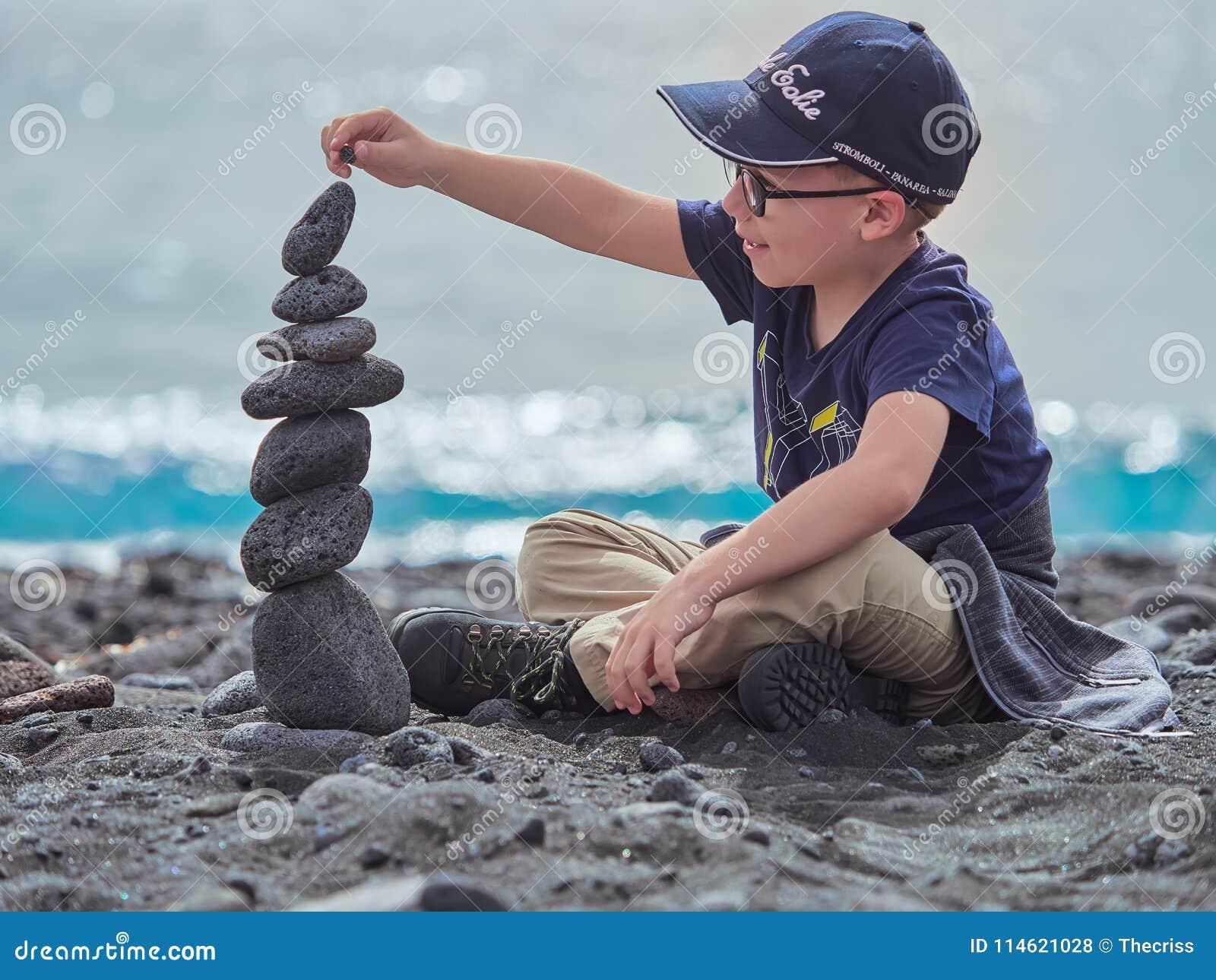 De jongensbouw steenstapel op het strand van Panarea, Eolische eilanden, Sicilië, Italië