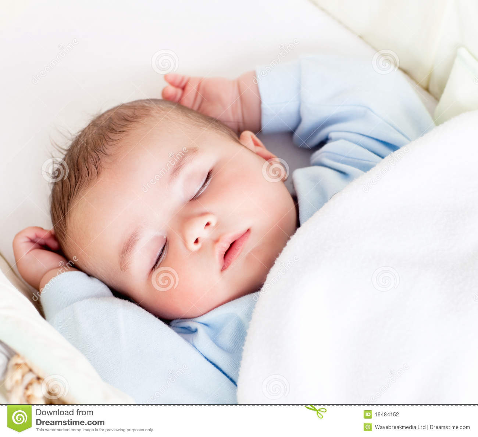 De jongensslaap van de baby vreedzaam in zijn wieg