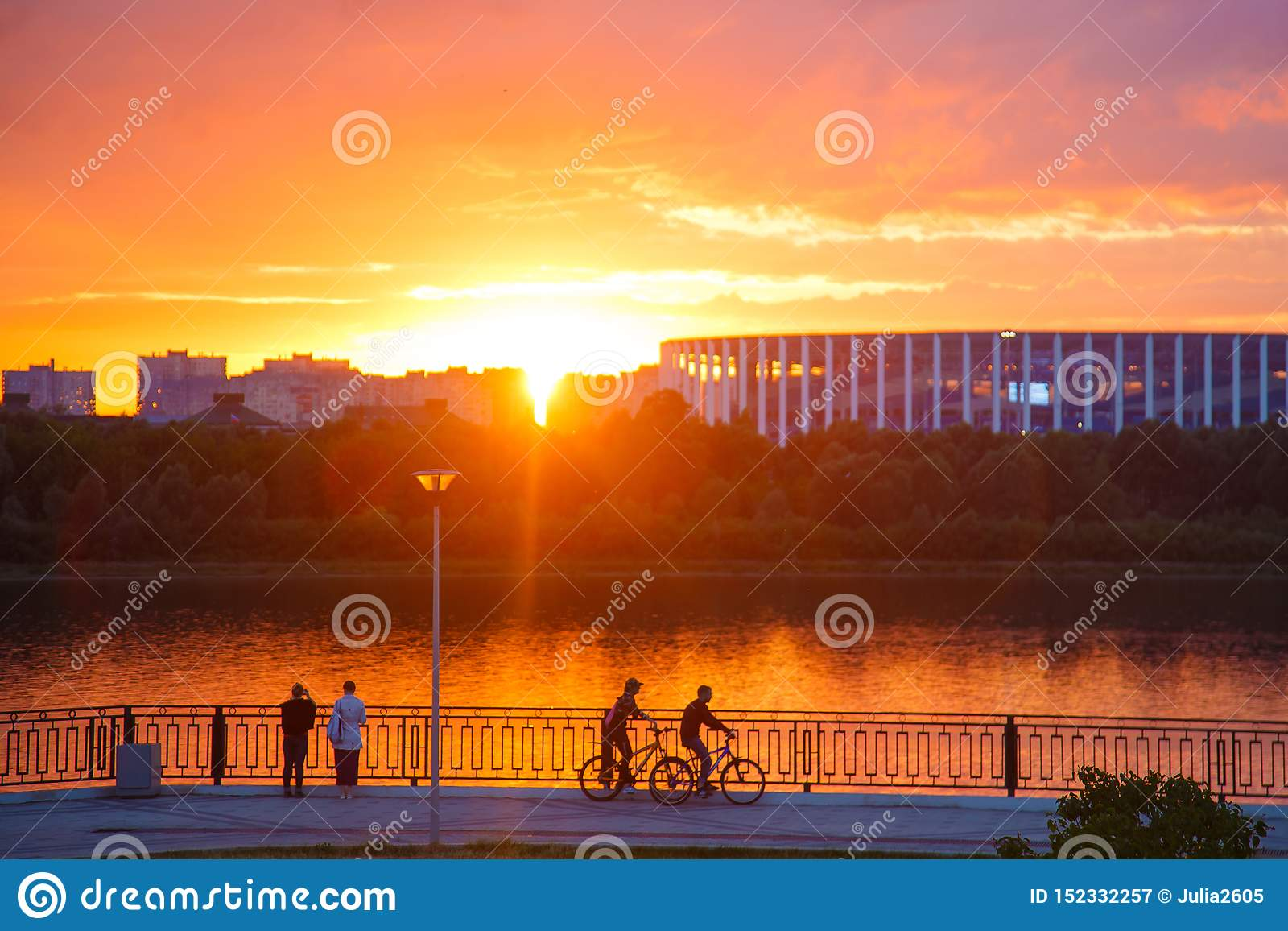De jongeren in de stad bij zonsondergang berijdt een fiets