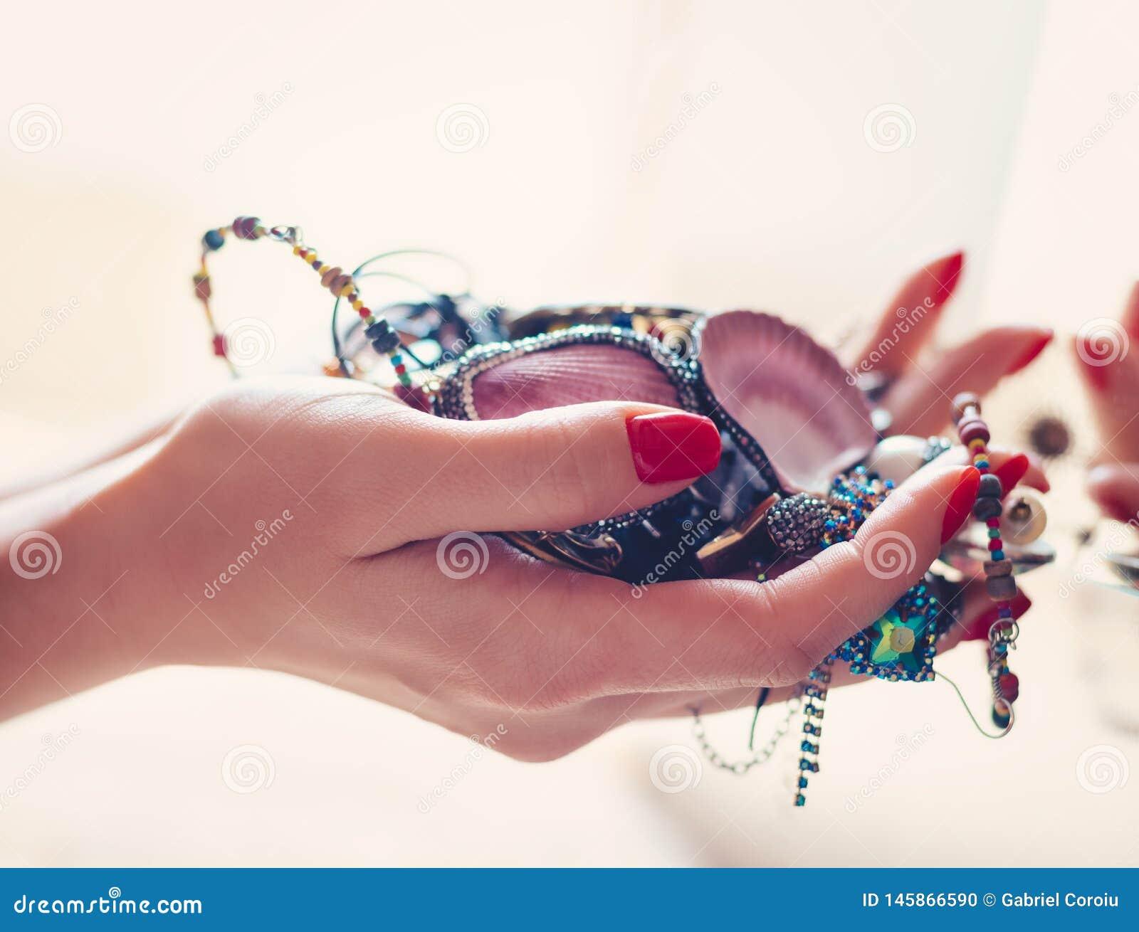 De juwelen van de vrouwenholding voor de spiegel