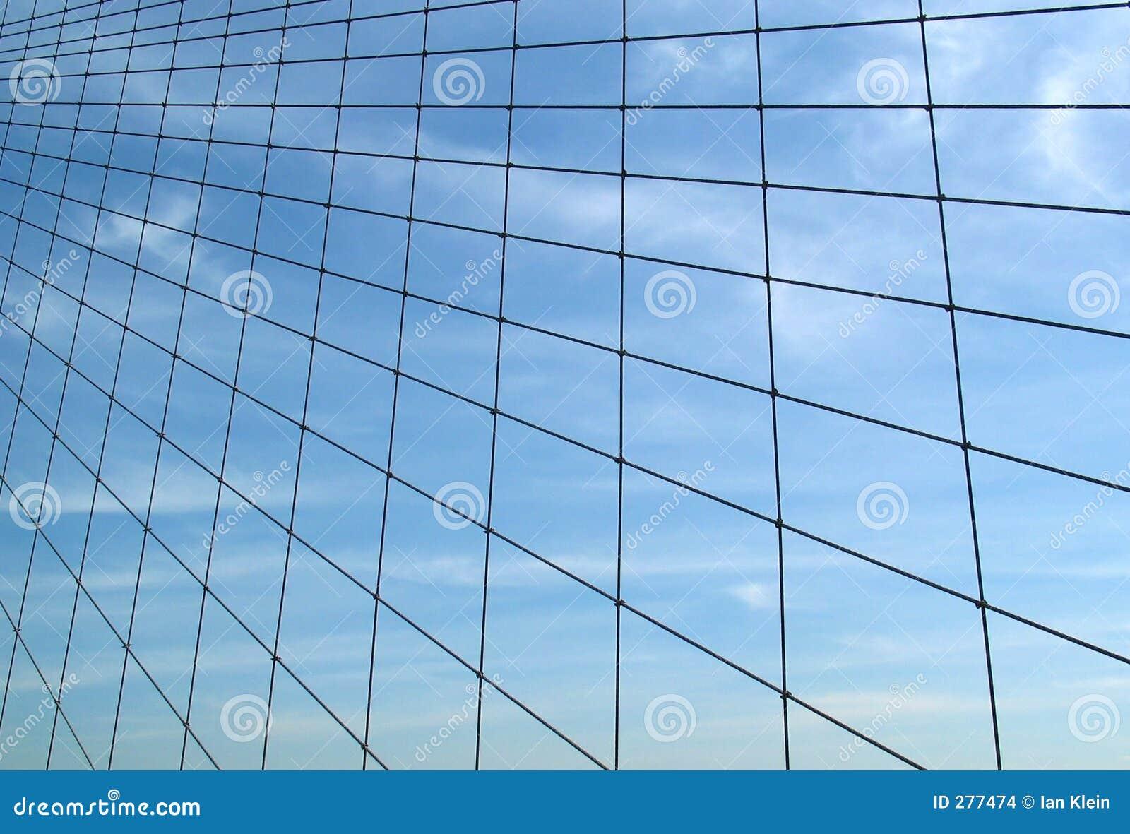 De Kabels van de Brug van Brooklyn tegen Hemel met Wolken Wispy