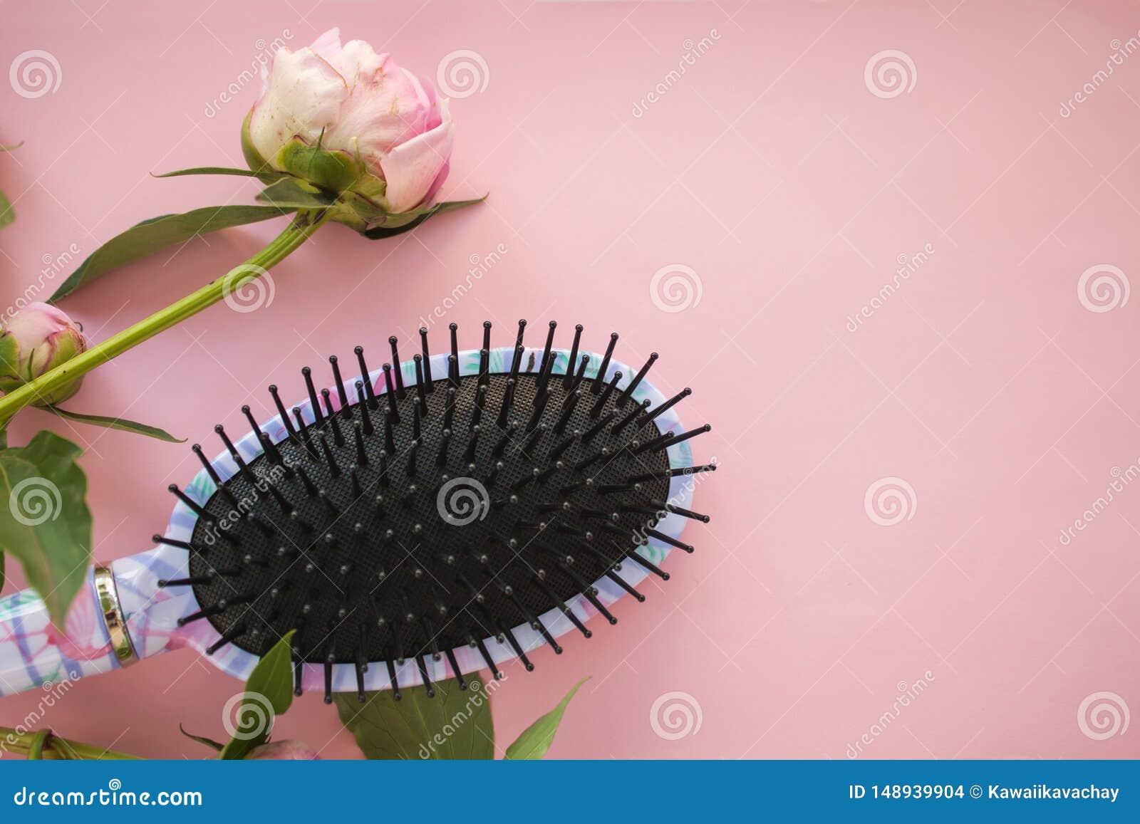 De de kamborstel van de haarmassage met pioenbloemen op roze pastelkleur kopieert ruimteachtergrond De Minimalisticvlakte lag