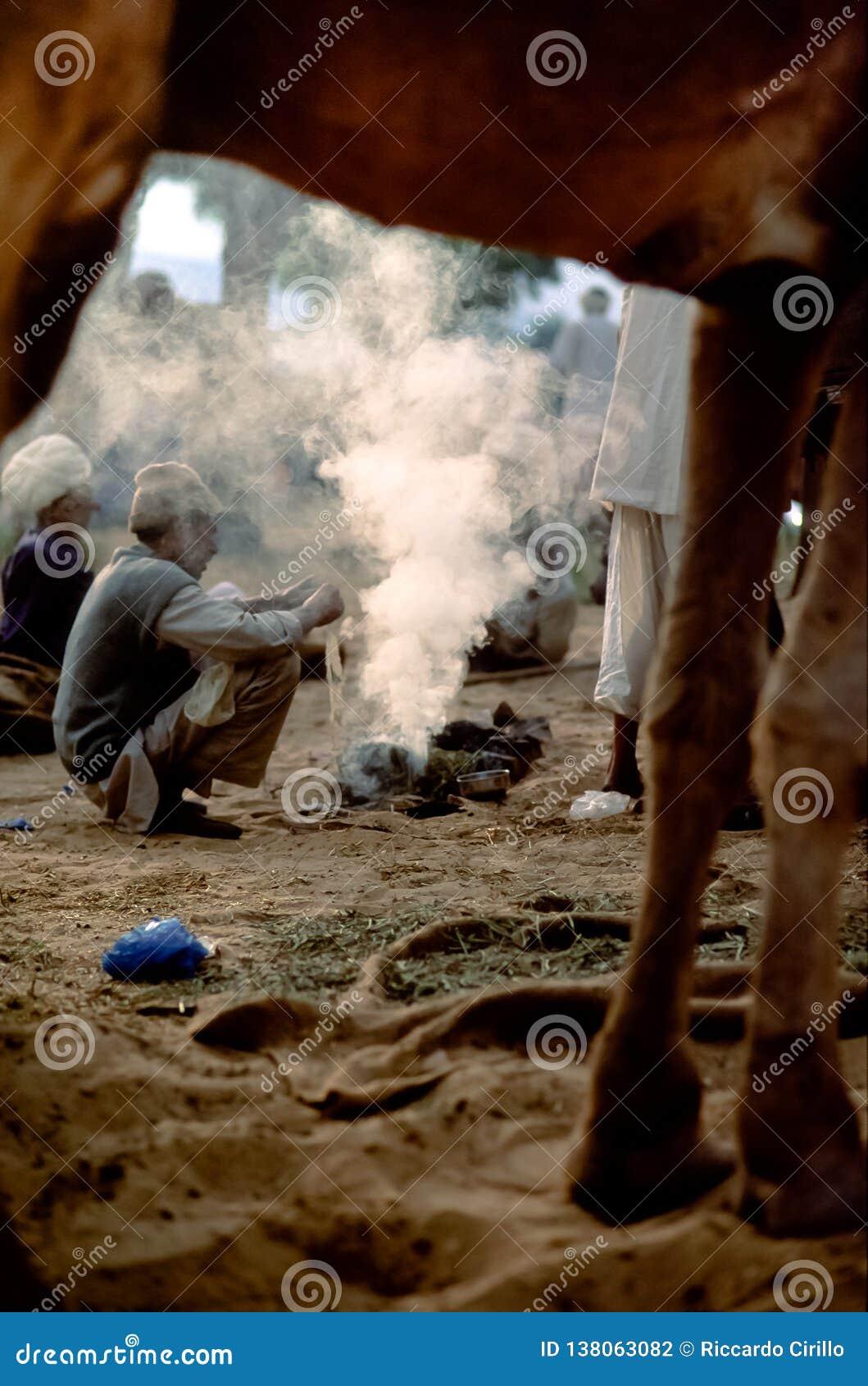 De kameelhandelaren hurken rond de sintels van een brand bij schemer, Pushkar Mela, Rajasthan, India
