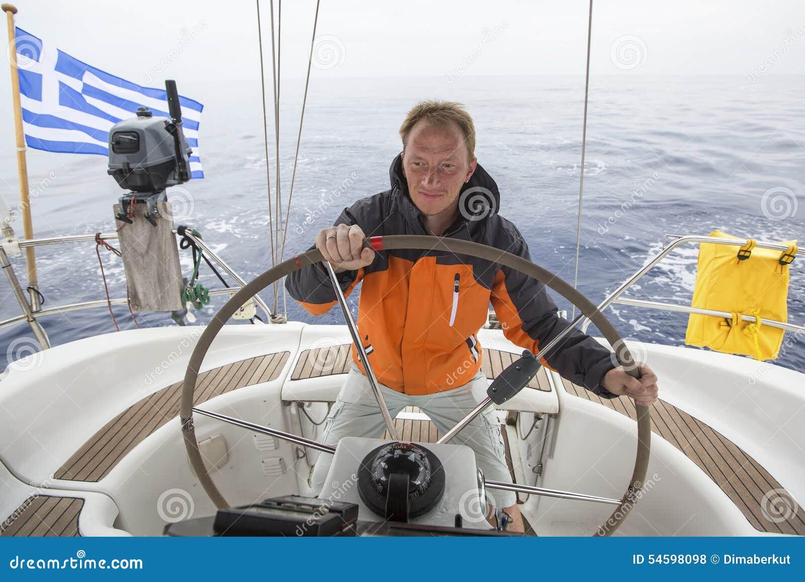 De kapitein drijft de zeilboot in de open zee yachting sailing