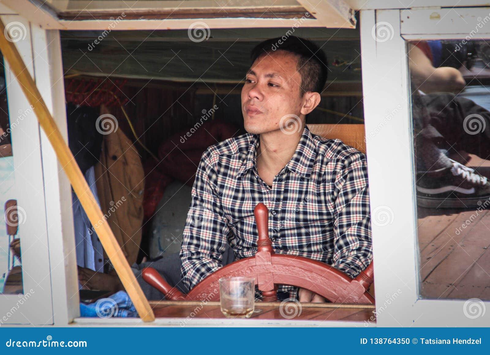 De kapiteinsAsian mens met donkere huid drijft een schip met een houten overzees stuurwiel