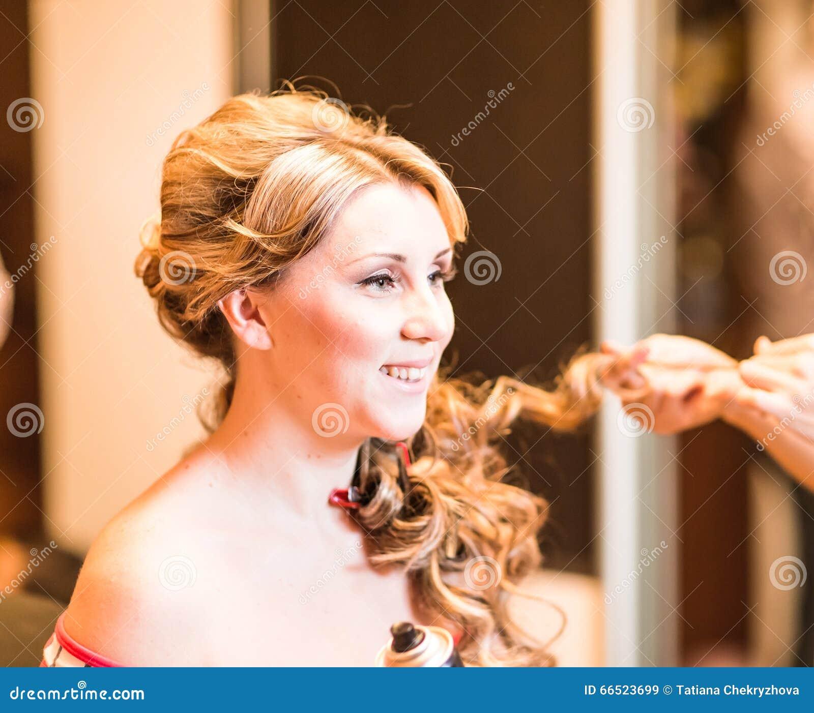 De kapper doet een kapsel aan de bruid