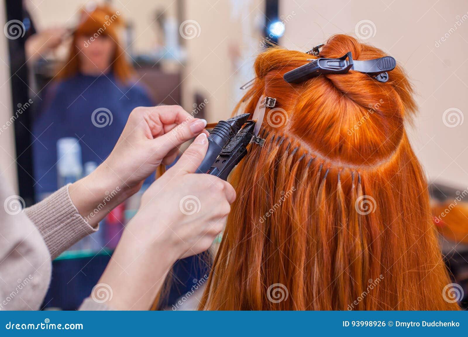 De kapper doet haaruitbreidingen aan een jong, roodharig meisje, in een schoonheidssalon