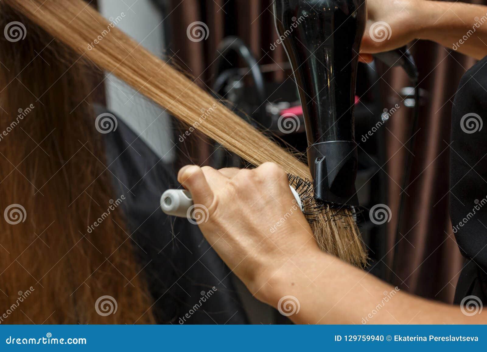 De kapper droogt haar aan de cliënt met een Hairdryer