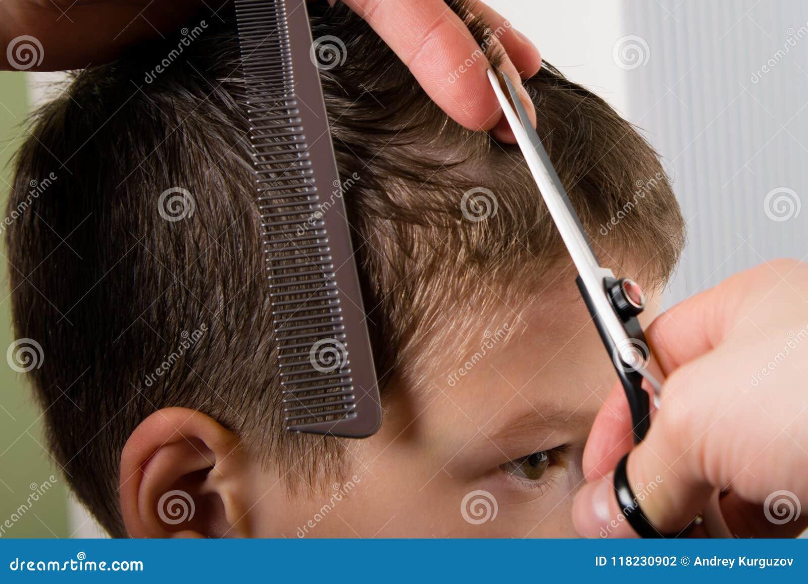 De kapper houdt een kam en een schaar in haar hand en maakt een kapseljongen
