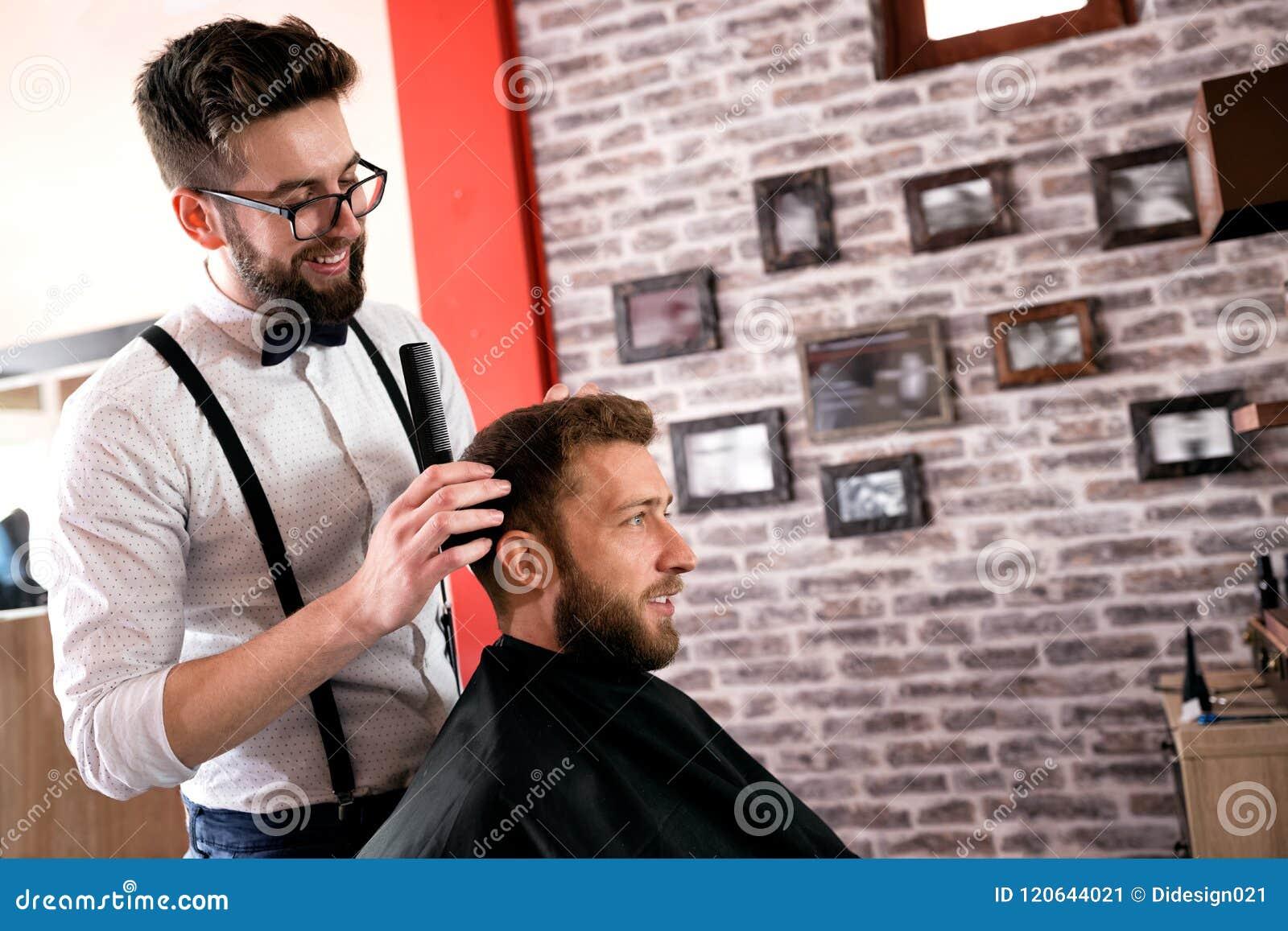 De kapper past haar aan een klant met een kam