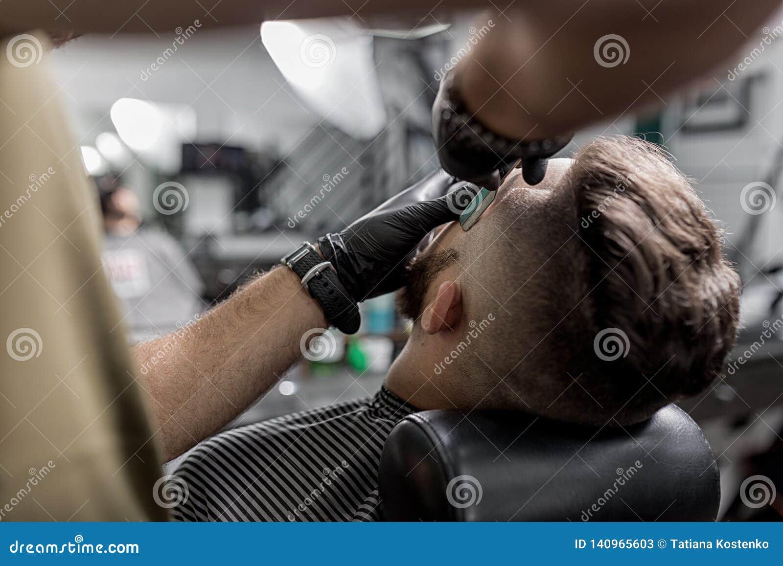 De kapper in zwarte handschoenen maakt tempel van de brutale gebaarde jonge mens met een recht scheermes bij een herenkapper in o