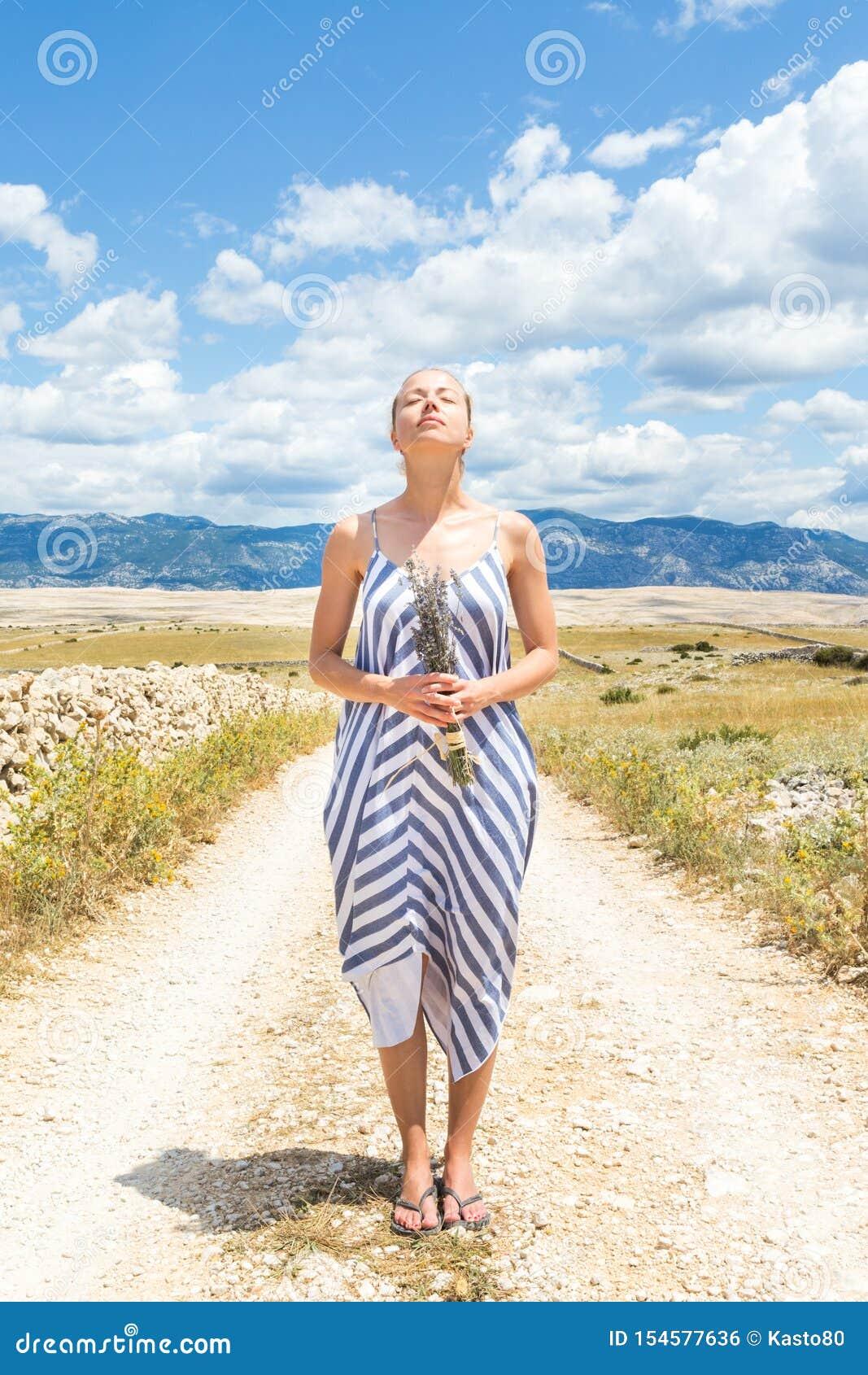 De Kaukasische jonge vrouw in de holdingsboeket van de de zomerkleding van lavendel bloeit het genieten van van zuivere Mediterra