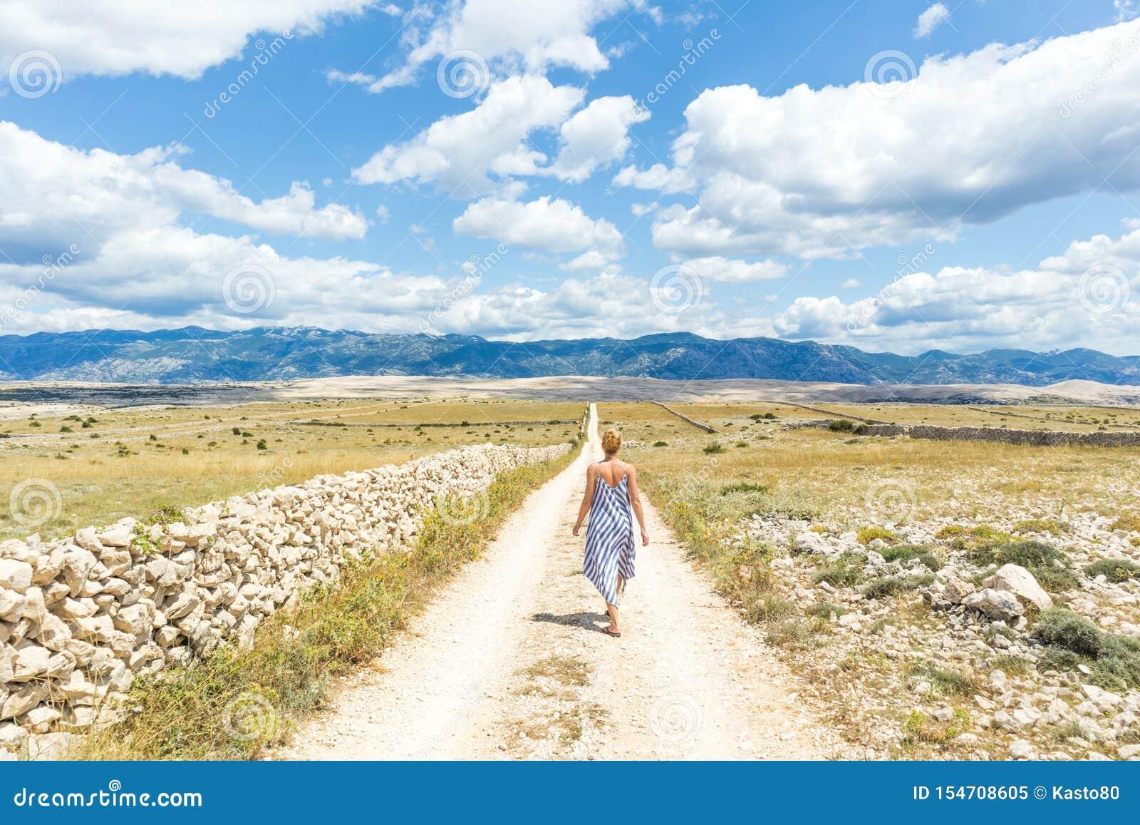 De Kaukasische jonge vrouw in de holdingsboeket van de de zomerkleding van lavendel bloeit terwijl lopen openlucht door droge rot
