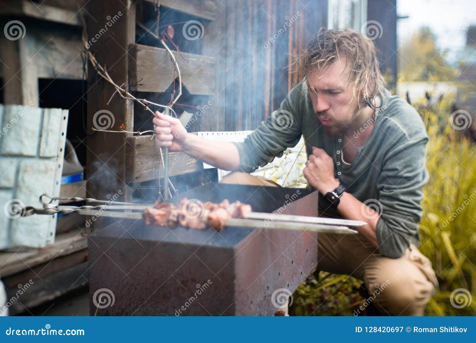 De kebabs van een mensengebraden gerechten op Mongal in zijn tuinperceel
