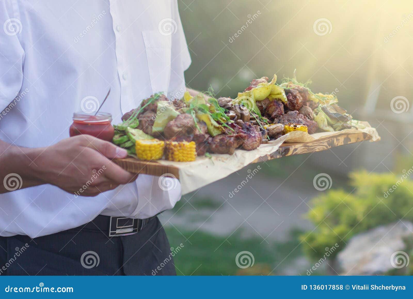 De kelner biedt geroosterde vlees en groenten bij zonnige dag aan