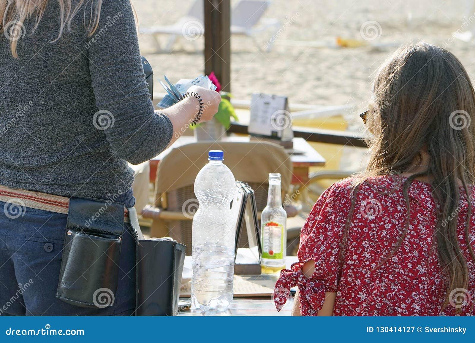 De kelner telt de klant in een koffie op het strand