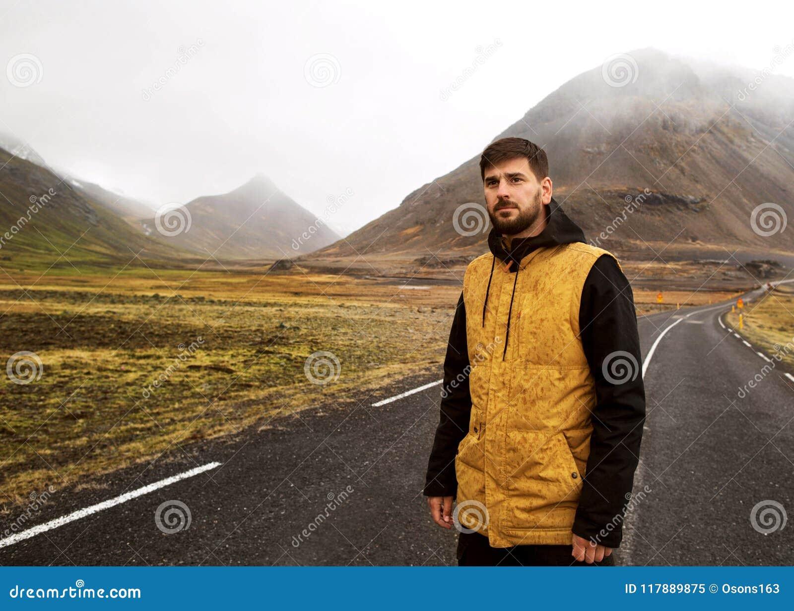 De kerel in een gele mantel loopt onderaan de weg in de bergen,