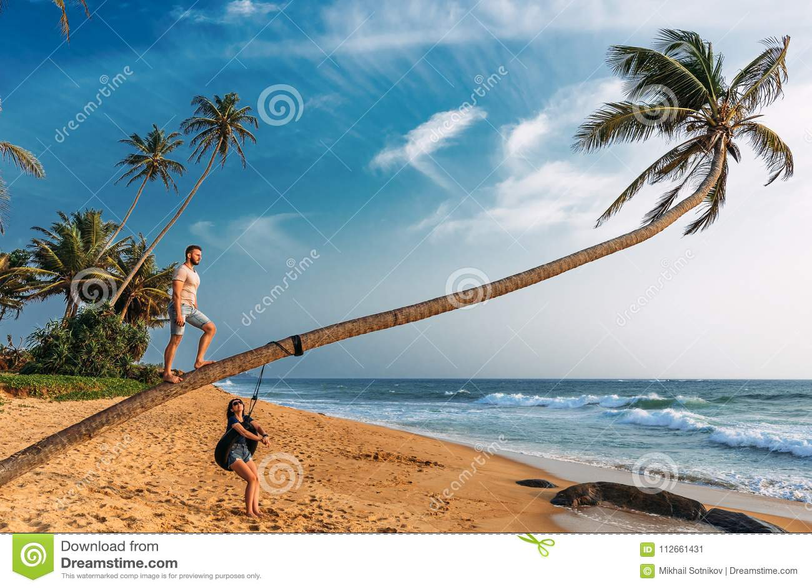 De kerel en het meisje dichtbij een palm op het strand ontmoeten de zonsondergang