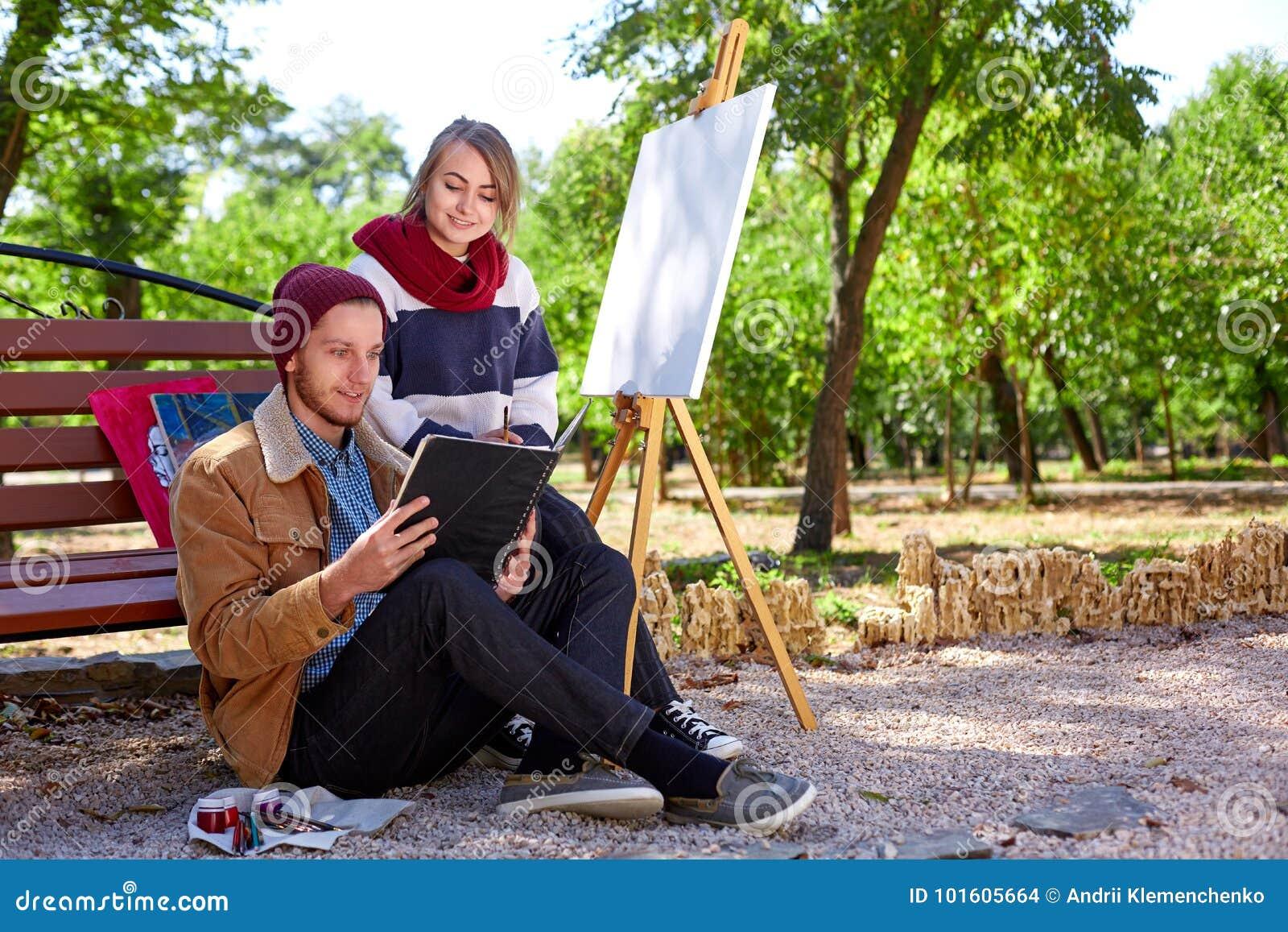 De kerel en het meisje letten op de beelden in hun album voor tekening