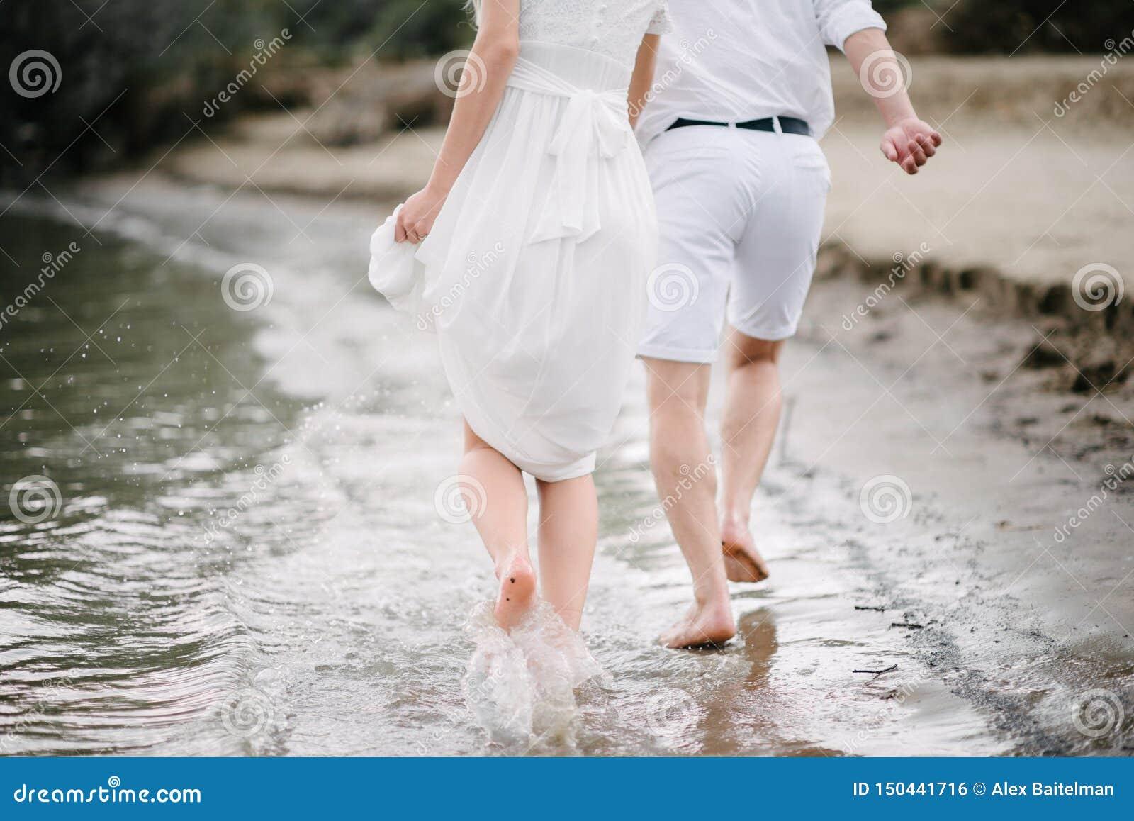 De kerel en het meisje lopen langs de kust
