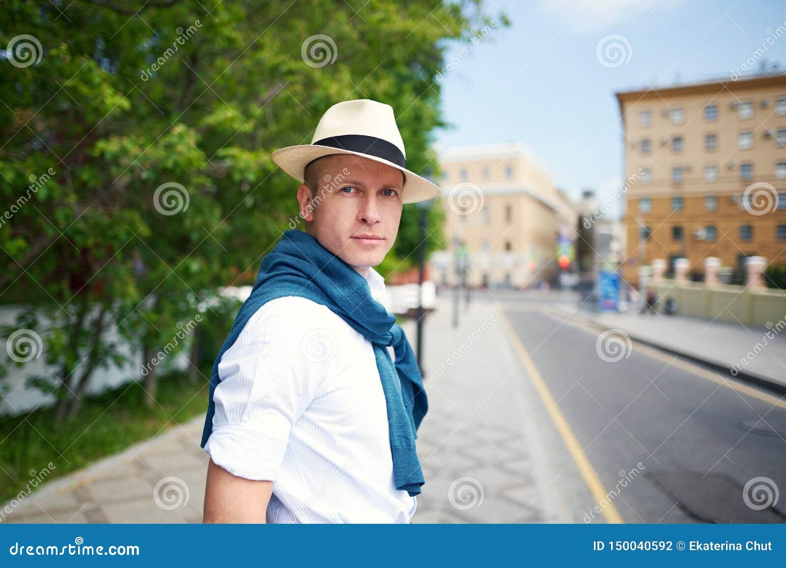 De kerel in de hoed op de straat