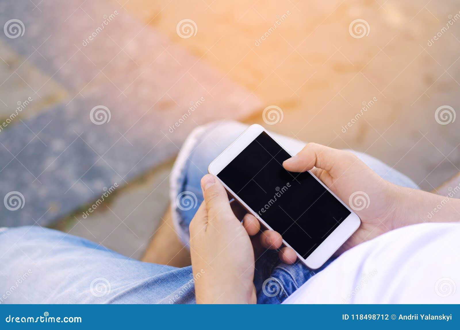 De kerel houdt een mobiele smartphone en bekijkt het scherm telefoonafhankelijkheid, sociale netwerken Het werk aangaande Interne
