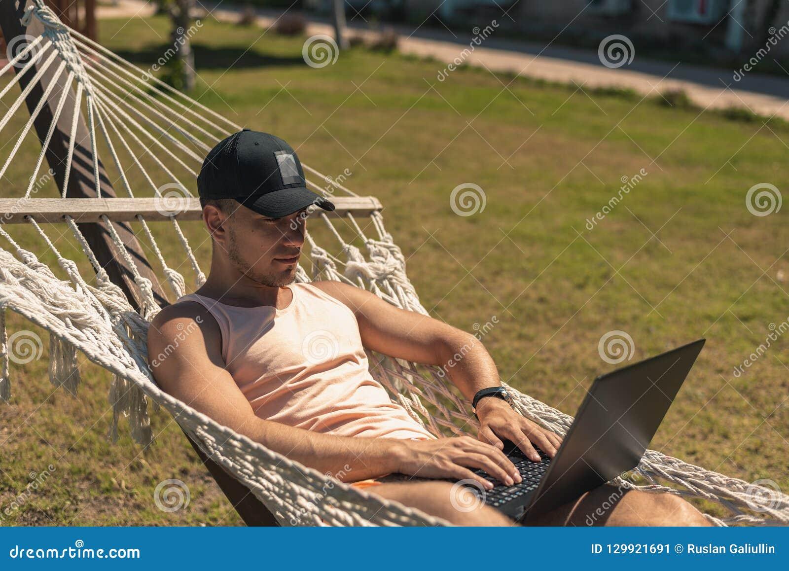 De kerel ligt in een hangmat met online laptop, mededeling, het werk, freelance, sociale netwerken, inkomens