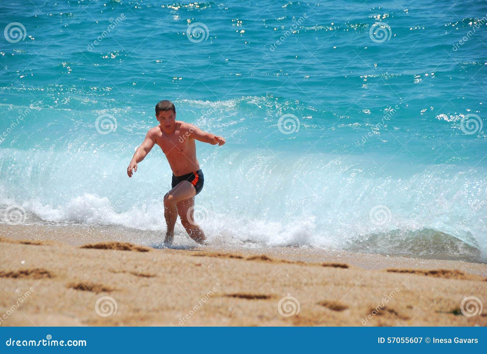 De kerel loopt vanaf de golven