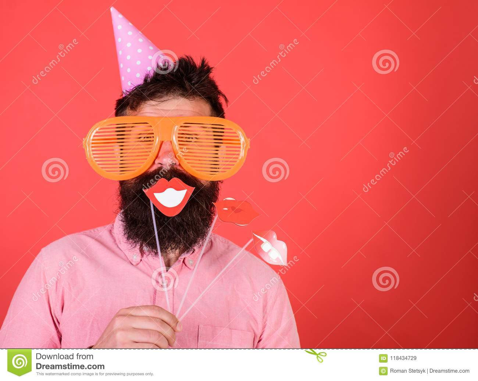 De kerel in partijhoed viert, stellend met fotosteunen Hipster in het reuzezonnebril vieren Mens met baard op vrolijk