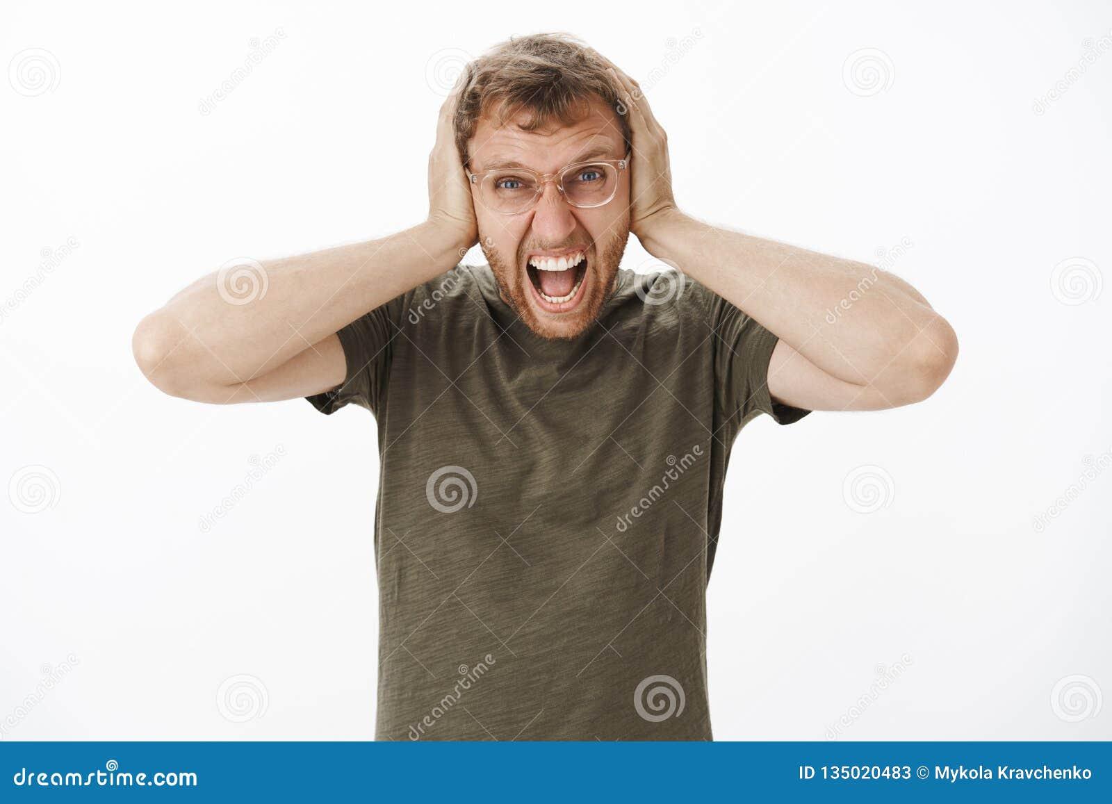 De kerel verliest bui die met hevig lawaai bij nacht schreeuwen zijn uit luid met boze verontwaardigingsuitdrukking die oren beha