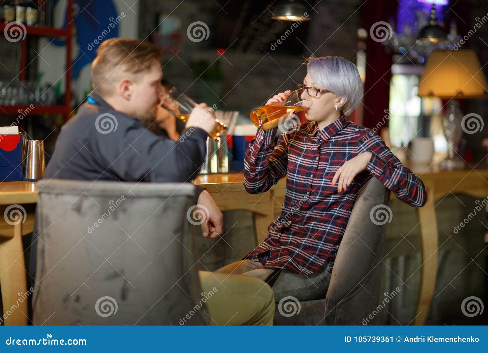 De kerels en een meisje drinken bierzitting in een bar binnen