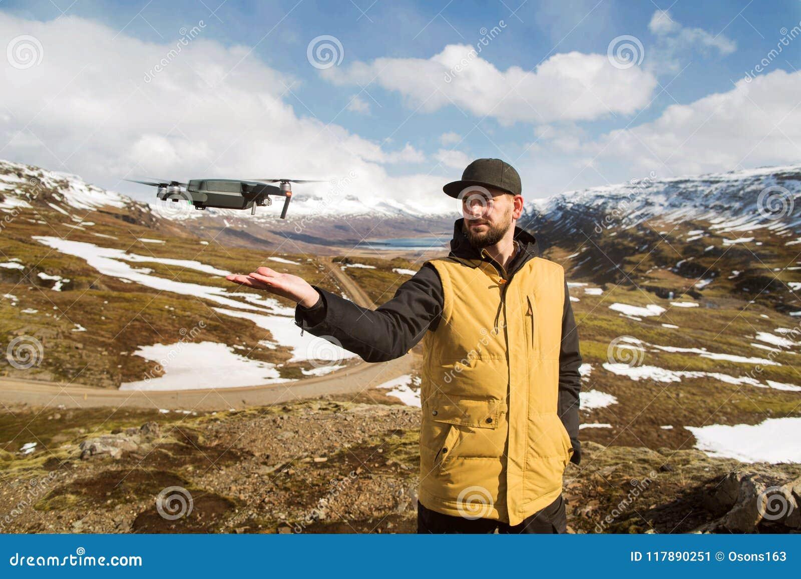 De kereltoerist lanceert quadrocopter met indient de bergen