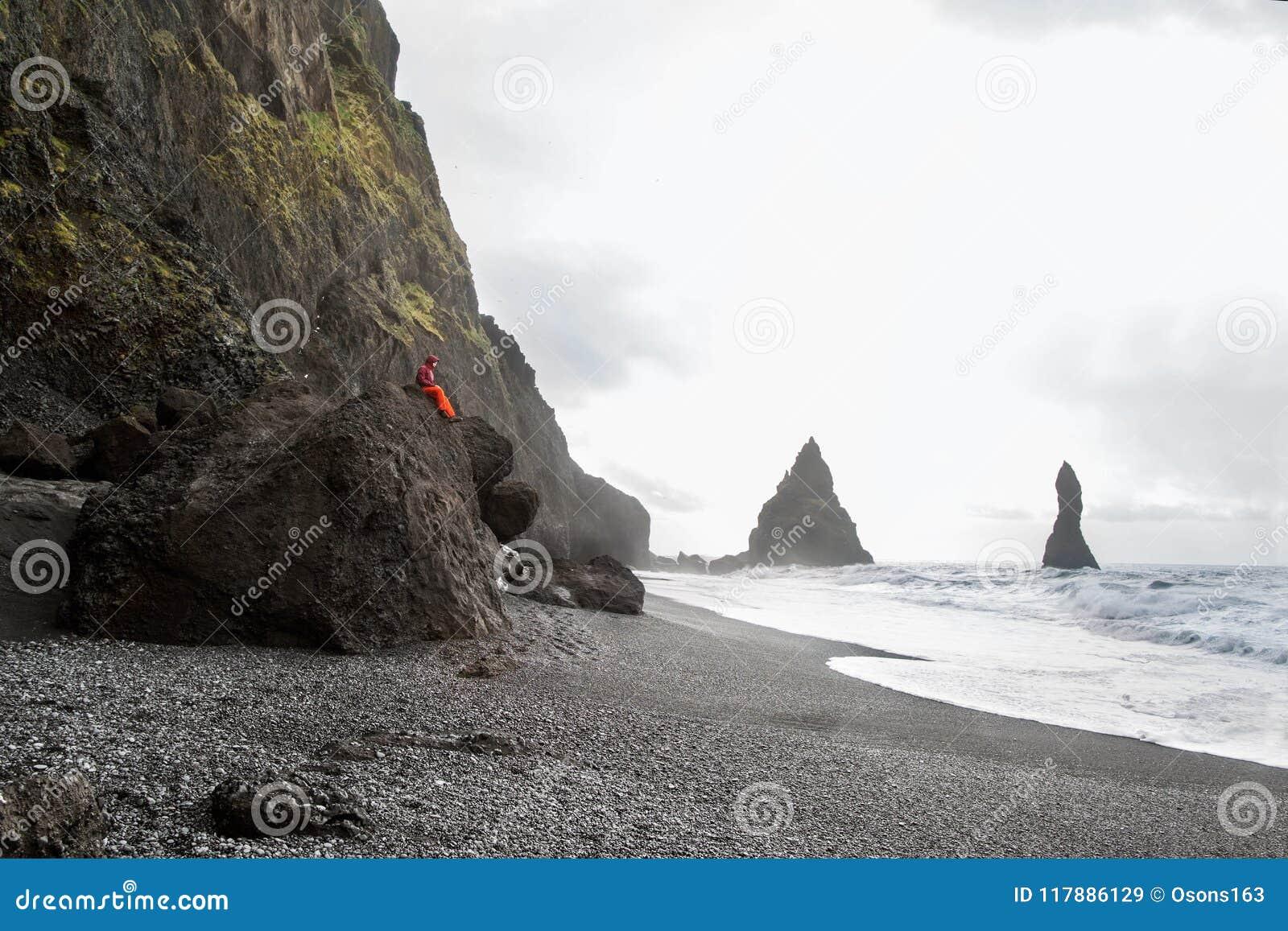 De kereltoerist zit bovenop een berg in IJsland, het concept van