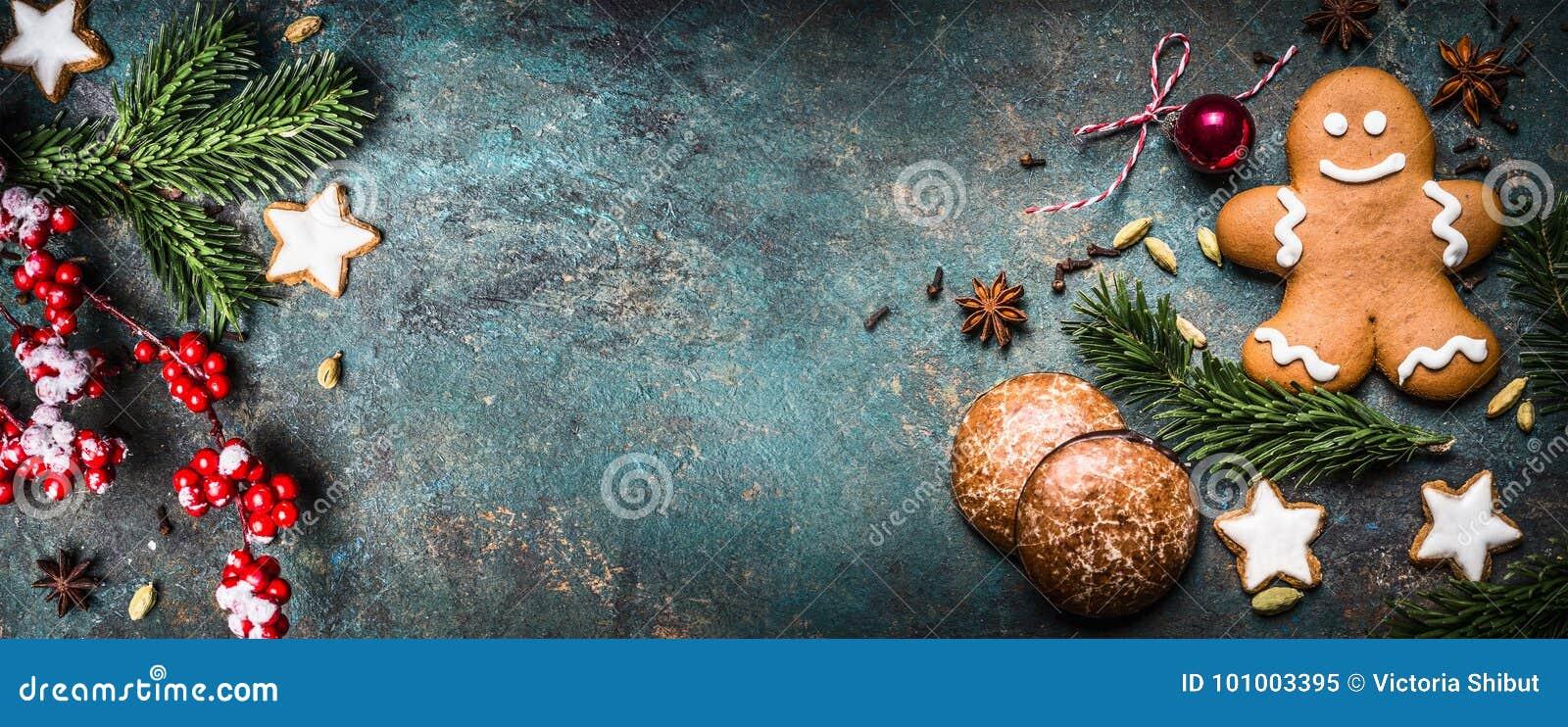 De Kerstmisachtergrond met feestelijke decoratie, koekjes, de peperkoekmens en spar vertakt zich hoogste mening, plaats voor teks