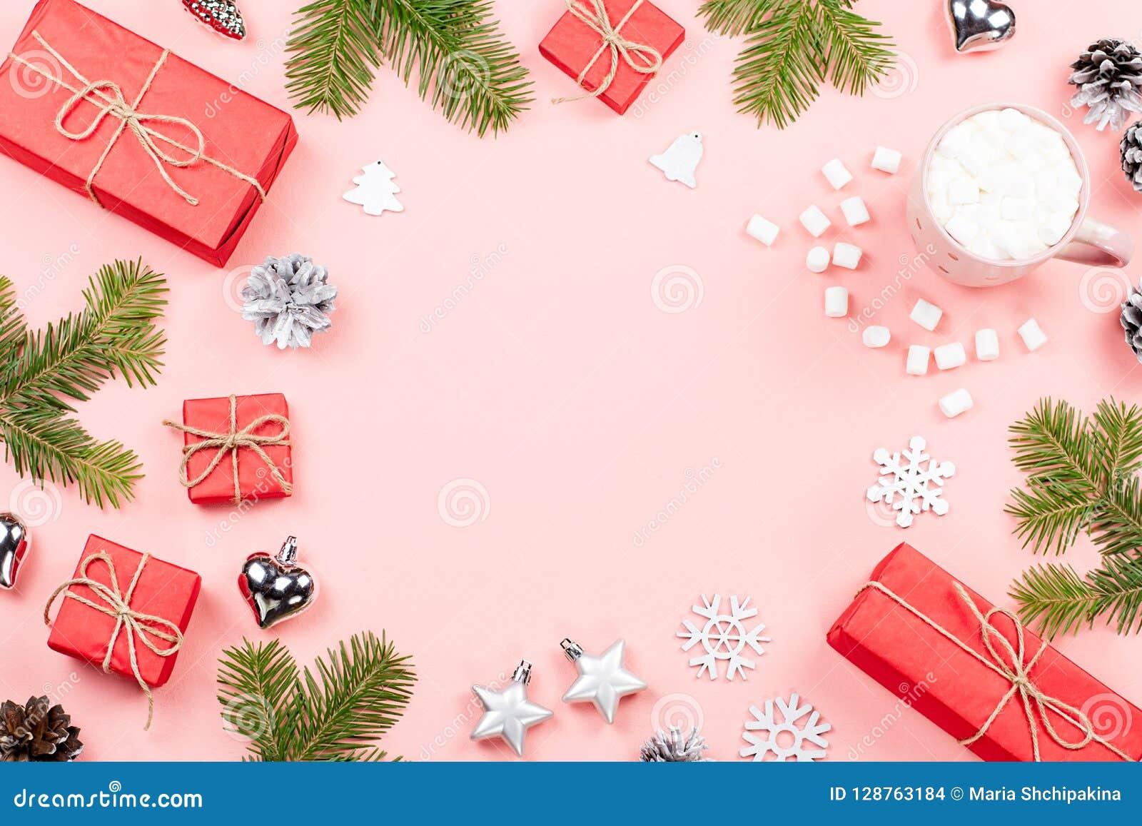 De Kerstmisachtergrond met spar vertakt zich, lichten, rode giftboxes, roze decoratie, hete drank met heemst op roze
