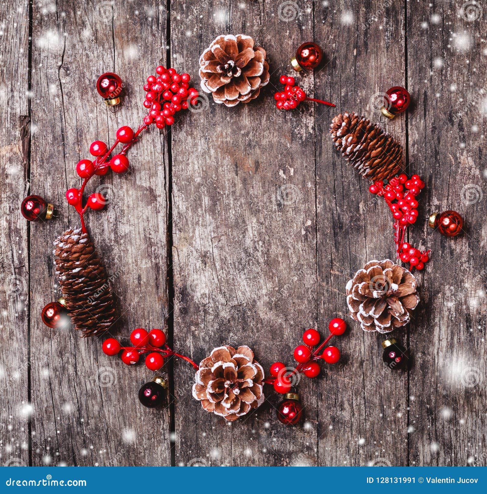 De Kerstmiskroon van Spar vertakt zich, kegels, rode decoratie op donkere houten achtergrond