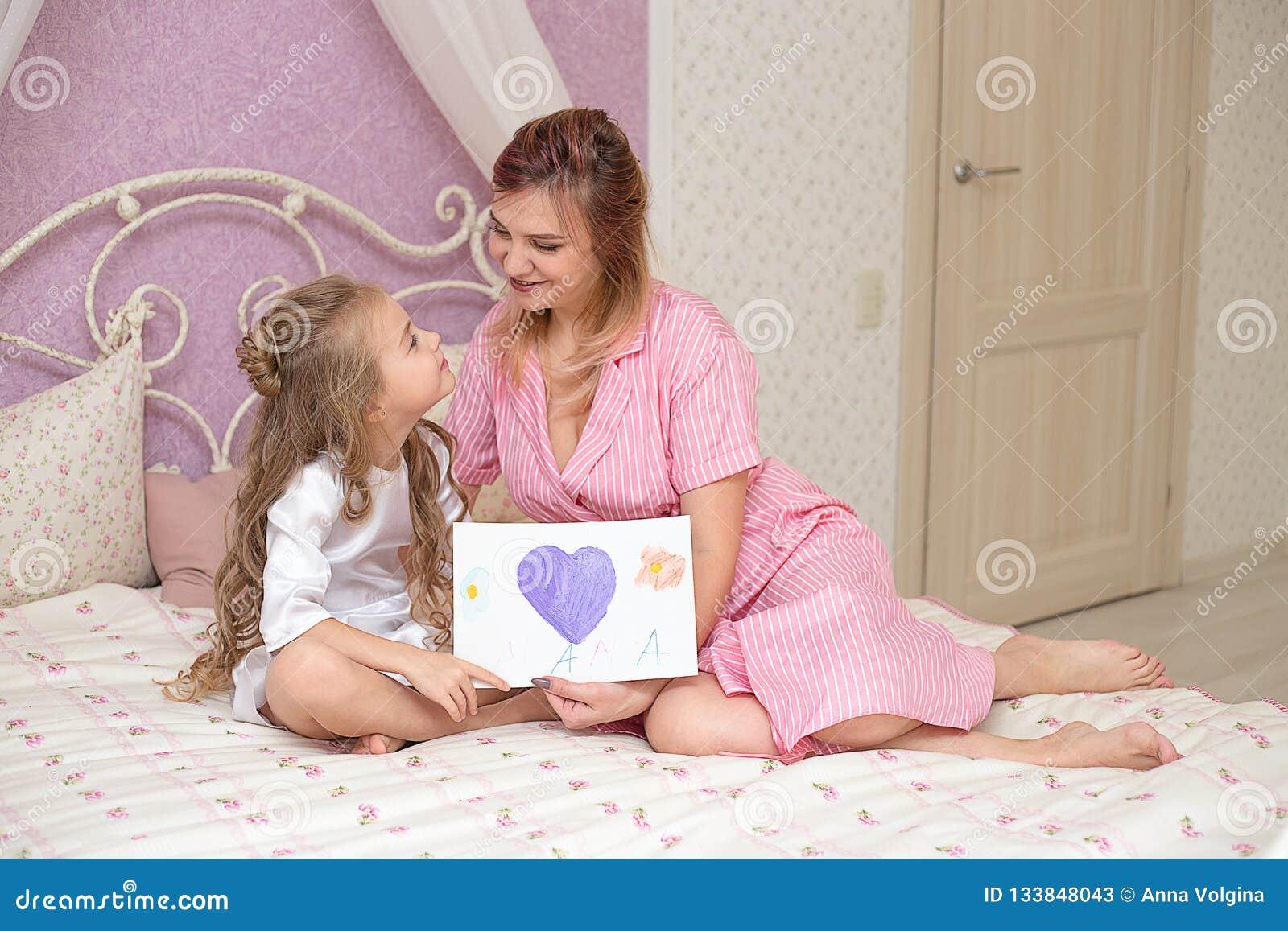 De kinddochter wenst mamma geluk en geeft haar een prentbriefkaar
