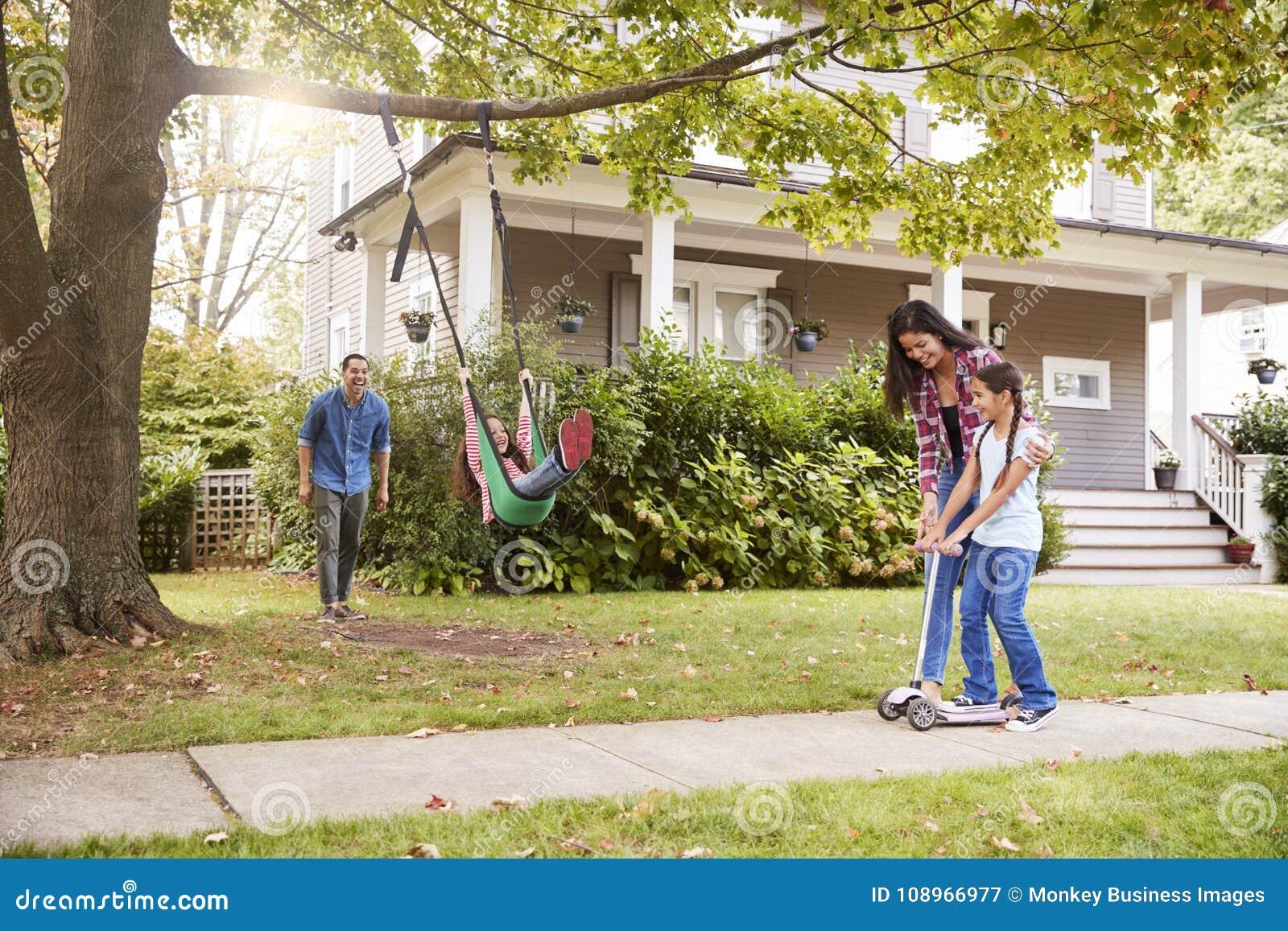 De kinderen die op Tuin spelen slingeren en Autoped buiten Huis