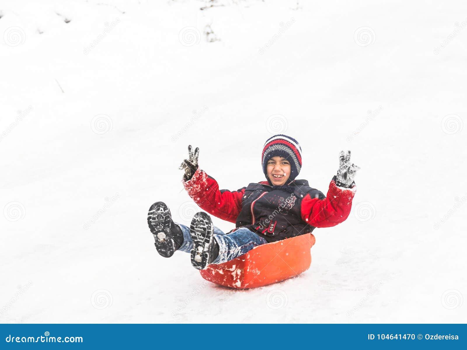 De kinderen glijden op sneeuw met plastic doos in Istanboel