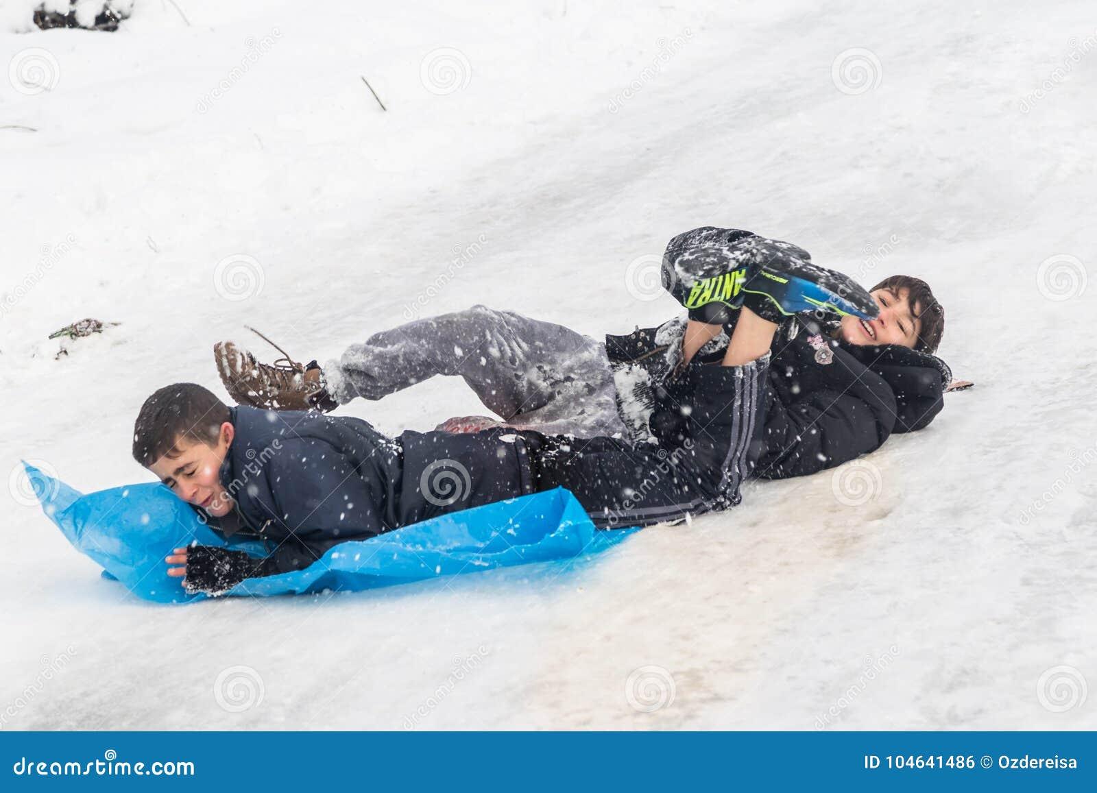 De kinderen glijden op sneeuw met plastic zak in Istanboel