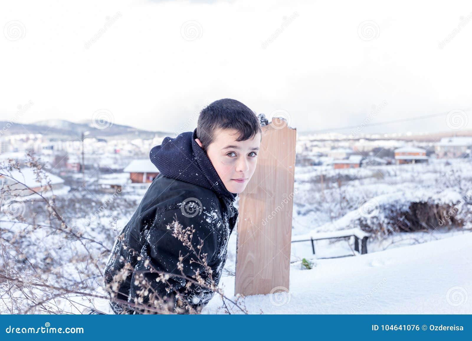 De kinderen glijden op sneeuw in oude schoolstijl met hardhout